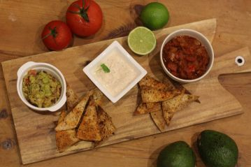 Guacamole, salsa, and soured cream dip with nachos