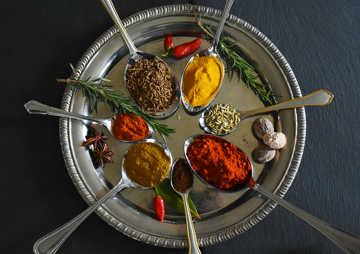 A silver platter placed on a slate board with 7 silver spoons full or spices of  range of colours (yellow, red, green).
